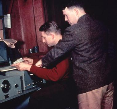 Hewlett-Packard Company co-founders David Packard (seated) and William Hewlett run final production tests on a shipment of the 200A audio oscillator. The picture was taken in 1939 in the garage at 367 Addison Avenue, Palo Alto, California, where they began their business.