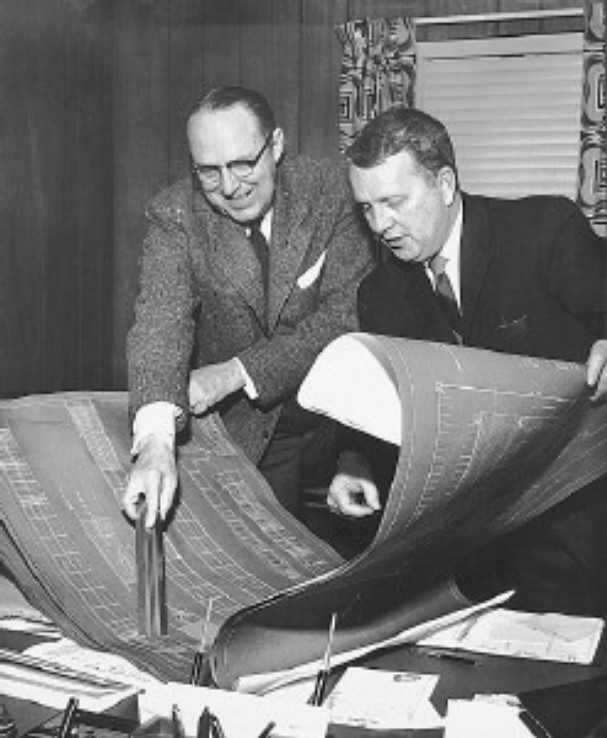 Holiday Inn leaders scout new project / Wallace E. Johnson (left), president, and Kemmons Wilson, chairman of the board of Holiday Inns of America Inc., look over plans for a new project in July 1958.